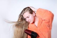 Muchacha adolescente que seca el pelo mojado largo usando hairdryer Foto de archivo