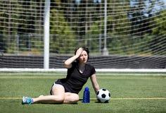 Muchacha adolescente que siente demasiado caliente en campo de fútbol en día caliente Imagen de archivo