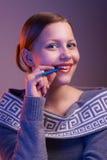 Muchacha adolescente que sonríe con la pluma en su mano, retrato Imagen de archivo libre de regalías