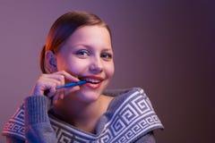 Muchacha adolescente que sonríe con la pluma en su mano, retrato Fotos de archivo