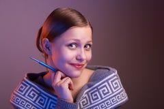 Muchacha adolescente que sonríe con la pluma en su mano, retrato Fotos de archivo libres de regalías