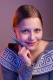 Muchacha adolescente que sonríe con la pluma en su mano, retrato Foto de archivo libre de regalías