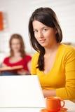 Muchacha adolescente que sonríe en la cámara con la computadora portátil Imagen de archivo