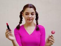 Muchacha adolescente que sostiene el lápiz labial y la piruleta Imágenes de archivo libres de regalías