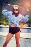 Muchacha adolescente que sostiene el monopatín Imagen de archivo