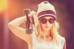 Muchacha adolescente que sostiene el monopatín Fotografía de archivo