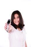 Muchacha adolescente que sostiene hacia fuera el teléfono celular Foto de archivo