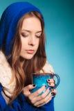 Muchacha adolescente que sostiene la taza azul con la bebida caliente Fotos de archivo libres de regalías