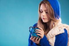 Muchacha adolescente que sostiene la taza azul con la bebida caliente Fotografía de archivo