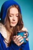 Muchacha adolescente que sostiene la taza azul con la bebida caliente Fotos de archivo