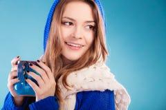 Muchacha adolescente que sostiene la taza azul con la bebida caliente Imágenes de archivo libres de regalías