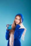 Muchacha adolescente que sostiene la taza azul con la bebida caliente Foto de archivo