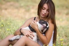 Muchacha adolescente que sostiene su perro feliz Imágenes de archivo libres de regalías