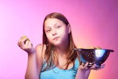 Muchacha adolescente que sostiene un colador lleno de manzanas y que come una manzana Fotos de archivo libres de regalías
