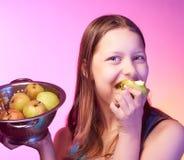 Muchacha adolescente que sostiene un colador lleno de manzanas y que come una manzana Imágenes de archivo libres de regalías