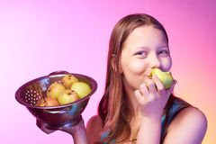 Muchacha adolescente que sostiene un colador lleno de manzanas y que come una manzana Foto de archivo libre de regalías