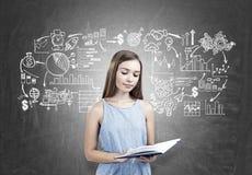 Muchacha adolescente que sostiene un libro, plan empresarial Foto de archivo