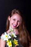 Muchacha adolescente que sostiene un ramo de narcisos y de sonrisas Foto de archivo libre de regalías
