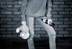 Muchacha adolescente que sostiene una botella de cerveza y el oso de peluche Foto de archivo libre de regalías