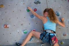 Muchacha adolescente que sube una pared de la roca interior Fotos de archivo