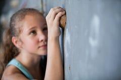 Muchacha adolescente que sube una pared de la roca interior Fotos de archivo libres de regalías