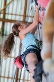 Muchacha adolescente que sube una pared de la roca interior Imágenes de archivo libres de regalías
