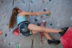 Muchacha adolescente que sube una pared de la roca interior Foto de archivo libre de regalías