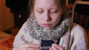 Muchacha adolescente que tiene una gripe o un frío Usando el termómetro, 4K UHD almacen de video