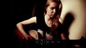 Muchacha adolescente que toca la guitarra en casa almacen de metraje de vídeo