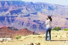 Muchacha adolescente que toma imágenes en Grand Canyon Imagen de archivo libre de regalías