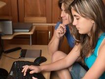 Muchacha adolescente que trabaja en un ordenador con su madre Foto de archivo libre de regalías
