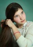 Muchacha adolescente que trenza el pelo grueso marrón largo Imágenes de archivo libres de regalías