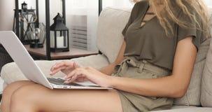 Muchacha adolescente que usa el ordenador portátil en el sofá almacen de video