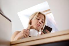 Muchacha adolescente que usa el teléfono celular en casa Fotografía de archivo libre de regalías
