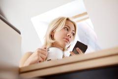 Muchacha adolescente que usa el teléfono celular en casa Imágenes de archivo libres de regalías