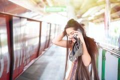 Muchacha adolescente que usa el teléfono móvil en la estación de la plataforma del tren Fotografía de archivo