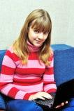 Muchacha adolescente que usa la computadora portátil en el país Imagen de archivo libre de regalías