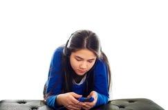 Muchacha adolescente que usa los auriculares en smartphone Imágenes de archivo libres de regalías