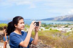 Muchacha adolescente que usa smartphone al vídeo en Hawaii soleada Fotos de archivo libres de regalías