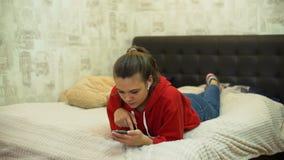 Muchacha adolescente que usa smartphone en la cama metrajes