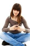 Muchacha adolescente que usa un teléfono celular Imagen de archivo libre de regalías