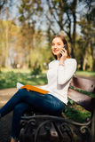 Muchacha adolescente que usa un teléfono elegante y mandando un SMS a sentarse con el cuaderno en un banco de un parque urbano Imagenes de archivo