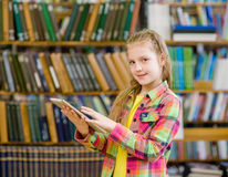 Muchacha adolescente que usa una tableta en una biblioteca Fotos de archivo