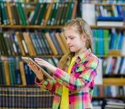 Muchacha adolescente que usa una tableta en una biblioteca Imagen de archivo