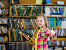 Muchacha adolescente que usa una tableta en una biblioteca y mostrando el pulgar Imagen de archivo