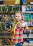 Muchacha adolescente que usa una tableta en una biblioteca y mostrando los pulgares para arriba Fotos de archivo libres de regalías
