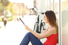 Muchacha adolescente que usa una tableta que se sienta en la calle Fotografía de archivo