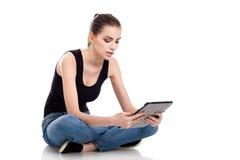 Muchacha adolescente que usa una tablilla Imágenes de archivo libres de regalías