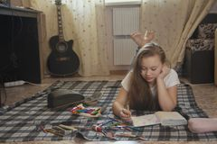 Muchacha adolescente quién pasan el tiempo en casa que dibuja bosquejos en un cuaderno mientras que mienten en el piso Fotos de archivo libres de regalías