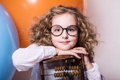 Muchacha adolescente rizada divertida, lista en vidrios con el ábaco de madera en t Fotos de archivo